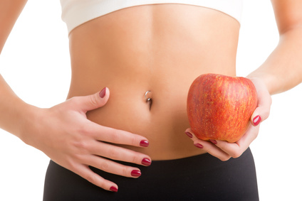 Woman holding an apple with a hand on her abdomen.