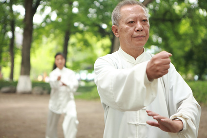 chinese man and woman doing taichi exercise outside