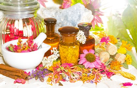 Naturopathy and aromatherapy still life with a pestle and mortar alongside fresh and dried flowers floral potpourri and essential oil extracts in bottles and celestine for crystal healing