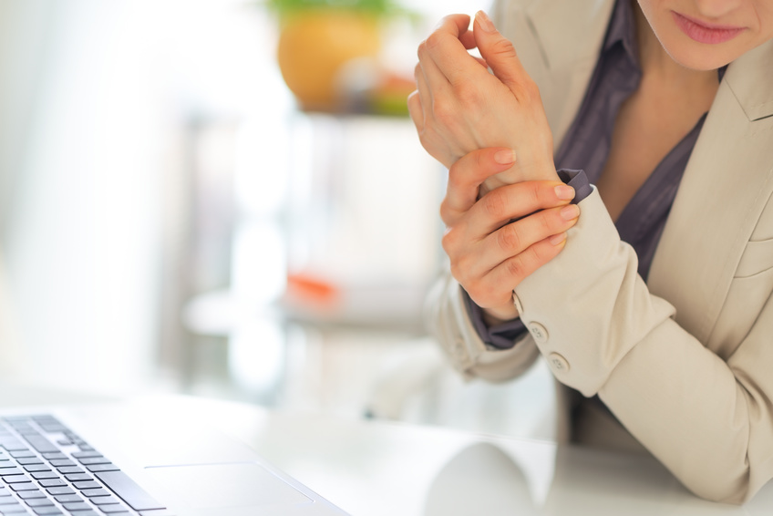 Closeup on business woman typingwith wrist pain