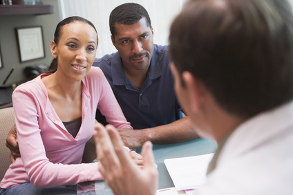 Couple having discussion with acupuncture doctor in IVF clinic sitting at desk