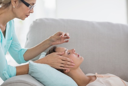 A female acupuncturist inserting an acupuncture needles to female patient's face.